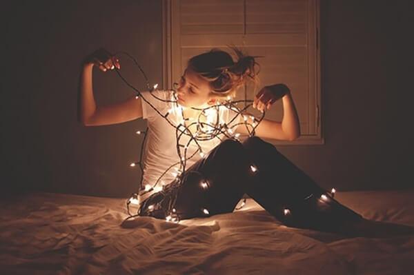 Menina com luzinhas natalinas para usar em ensaios fotográficos