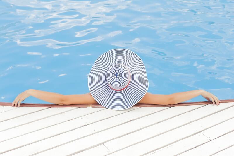 Mulher de costas e de chapéu na piscina