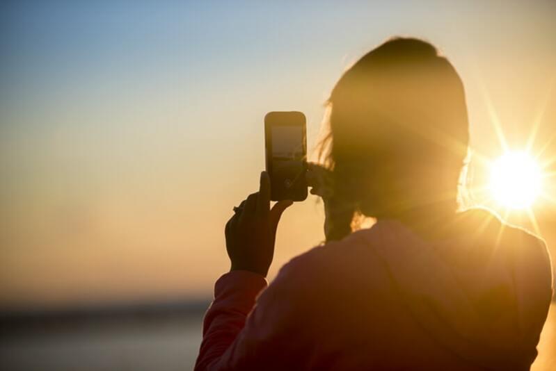 Menina tirando fotos do pôr do sol