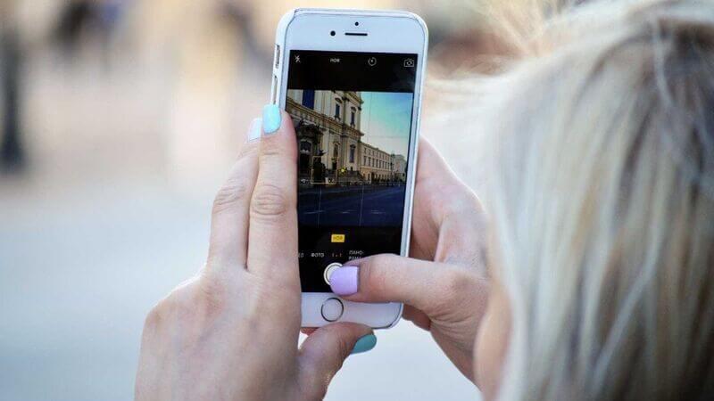 Mãos segurando celular capturando foto