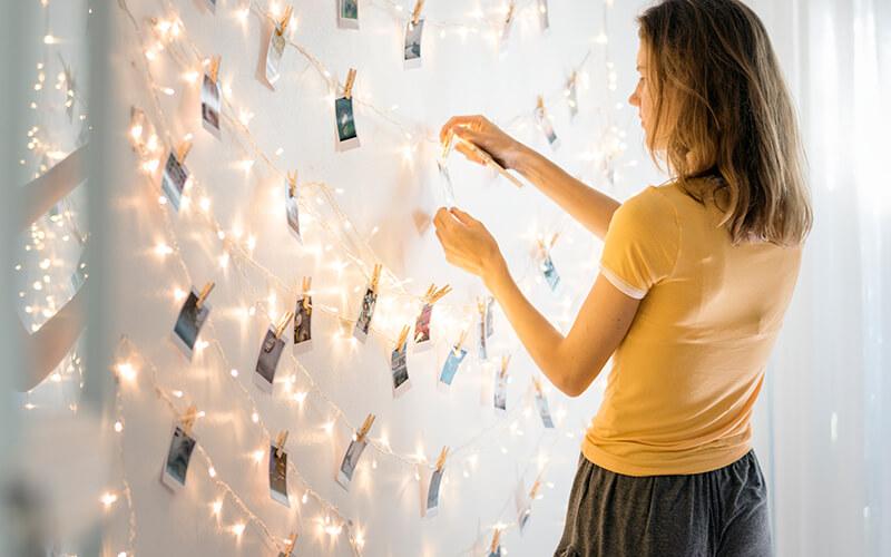 Mulher colocando foto em mural de fotos polaroid